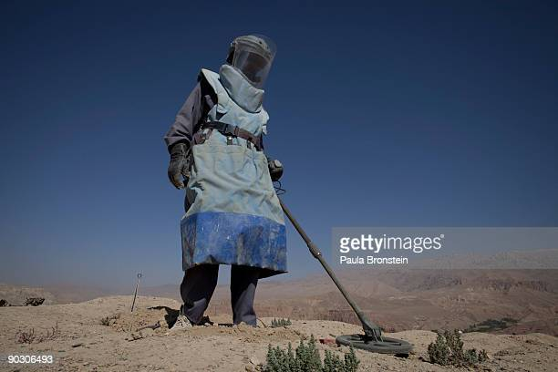 An Afghan deminer uses a metal detector to search for ordinance on top the archaelogical site of Shahr-i-Gholghola September 2 , 2009 in Bamiyan,...