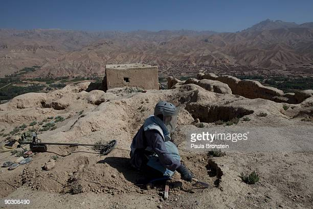 An Afghan deminer uses a small shovel to search for ordinance on top the archaelogical site of Shahr-i-Gholghola September 2 , 2009 in Bamiyan,...