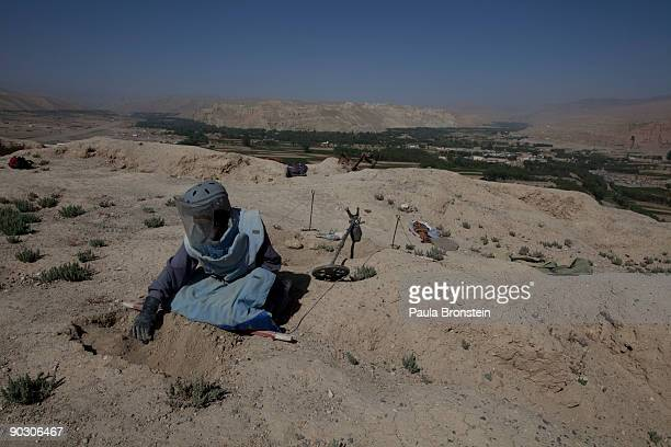 An Afghan deminer uses his hand to slowly dig searching for ordinance on top the archaelogical site of Shahr-i-Gholghola September 2 , 2009 in...