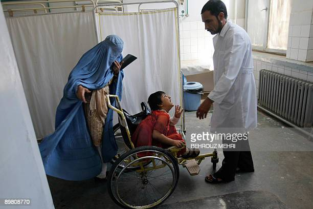 An Afghan Doctor speaks to a mentally disabled girl at the Emergency Ward of Herat Hospital in the western city of Herat on August 15 2009...