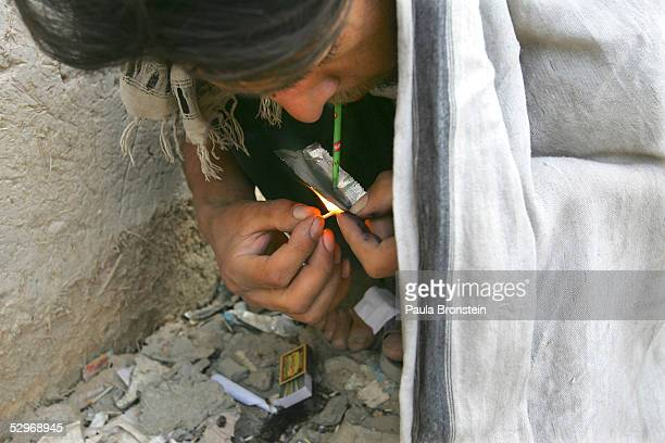 An Afghan drug user smokes heroin on May 20 2005 in Kabul Afghanistan UN experts have warned that the country is turning into a narcostate less than...