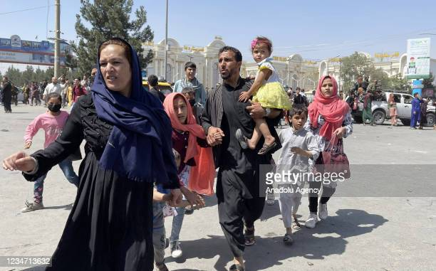 An Afghan family rushes to the Hamid Karzai International Airport as they flee the Afghan capital of Kabul, Afghanistan, on August 16, 2021.