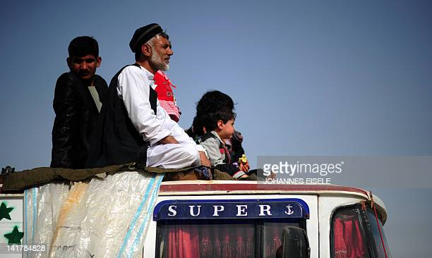 An Afghan family sits on a truck to watch the traditional Afghan sport Buzkashiin Mazari Sharif on March 23 2012 The ancient game of Buzkashi is an...