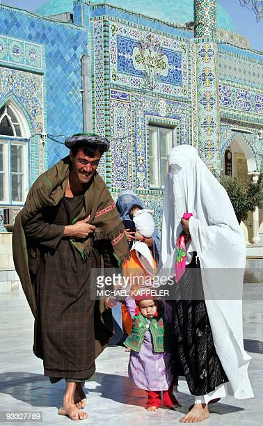 An Afghan family walks in front of the shrine of HazratiAli also called the Blue Mosque in MazariSharif the capital of Balkh province north of Kabul...