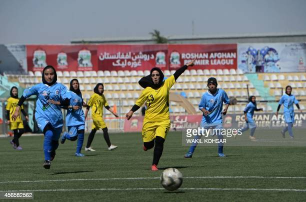An Afghan female football player of Kabul team vies for the ball with her Herat opponent in the final match at the Afghanistan Football Federation...