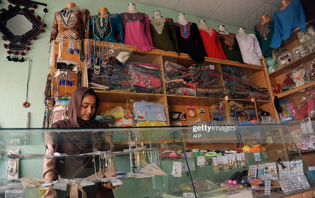 An Afghan female shopkeeper arranges products on the shelf at store in 'Rabia Balkhi', an all women market, on Chedgari Street in Mazar-e-Sharif province on April 25, 2013. The Rabia Balkhi women's market houses about 20 women-owned stores that sell a range of goods from handicrafts to beauty supplies and photography equipment, and is named after the famous princess and poet Rabia Balkhi or Rabia Qozdari who lived in the city of Balkh during the 9th century. AFP PHOTO/ Farshad USAYAN