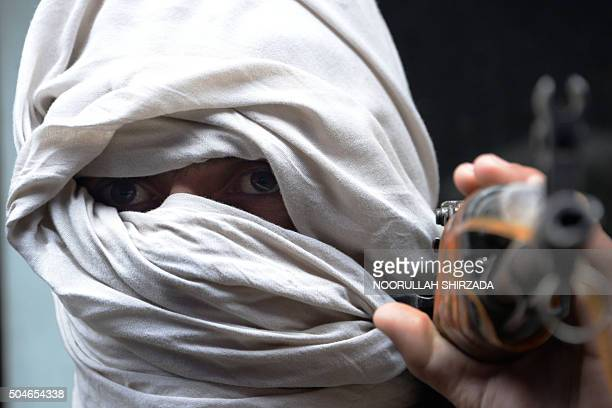 An Afghan former Taliban fighter carries his weapon before handing it over as part of a government peace and reconciliation process at a ceremony in...