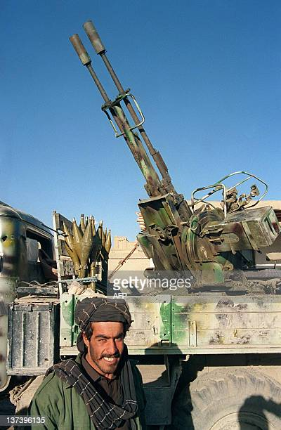 An Afghan from the religious Taliban militia stands in front of a 23mm truckmounted antiaircraft gun part of the massive arsenal of heavy weapons...