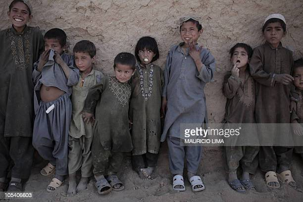 An Afghan girl blows bubble gum as she stands with boys during rollcall before start to work around a bazaar area just outside a US Marines combat...