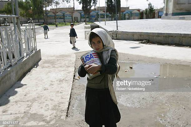 An Afghan girl carries a can of US AID donated cooking oil home from school through the memorial tomb of Pashtun leader Ahmad Shah Baba March 1 2005...