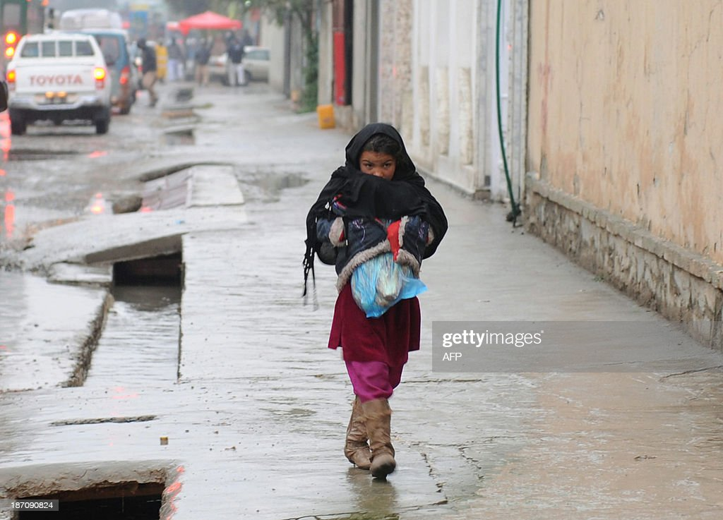 An Afghan girl carries bread as she walks through her neighbourhood on a rainy day in Kabul on November 6, 2013. Despite massive injections of foreign aid since the fall of the Taliban in 2001, Afghanistan remains desperately poor as it attempts to recover from decades of conflict. AFP PHOTO / Farshad USYAN