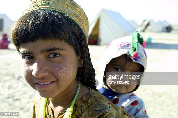 An Afghan girl carries her baby sister on her back at the Mile 46 refugee camp about five kilometers inside Afghanistan south of the Iranian city of...