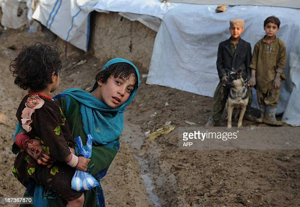 An Afghan girl carries her sister as she looks on at a refugee camp in CharaheQambar neighbourhood of Kabul on November 8 2013 Most families were...