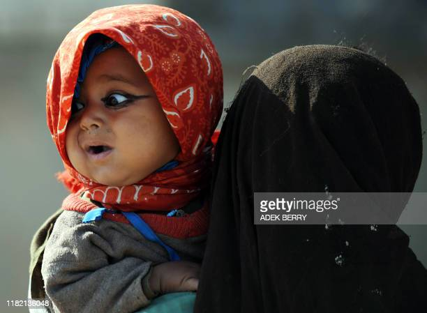 An Afghan girl cradles her younger sister in Garmser, Helmand Province, on March 7, 2011. There are around 140,000 international troops, two-thirds...
