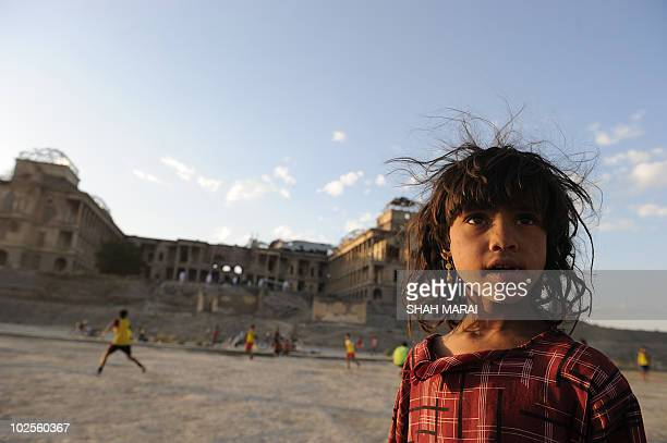 An Afghan girl Frishta begs for money as youths play football in front of the wardamaged Darlaman Palace in Kabul on June 10 2010 AFP PHOTO/SHAH Marai