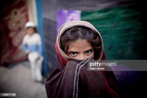 An Afghan girl from Kapisa province stands outside a tent in a camp October 21 2010 east of Kabul Afghanistan People from the restive Kapisa province...