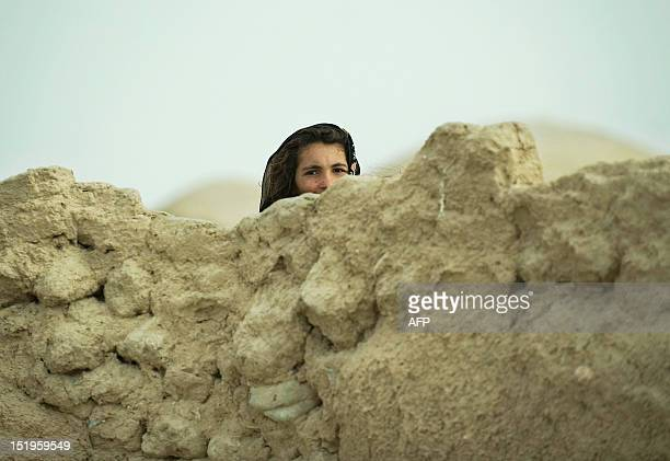 An Afghan girl from the local Pashtun tribe peers from behind a mud perimeter wall to watch US Army soldiers from the 1st Platoon Delta Coy 164 ARS...