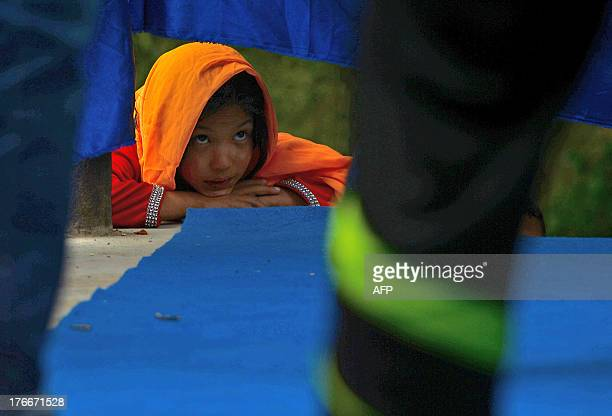 An Afghan girl from the Mobile Mini Circus for Children looks at her colleagues performing during a show in Paghman district on the outskirts of...