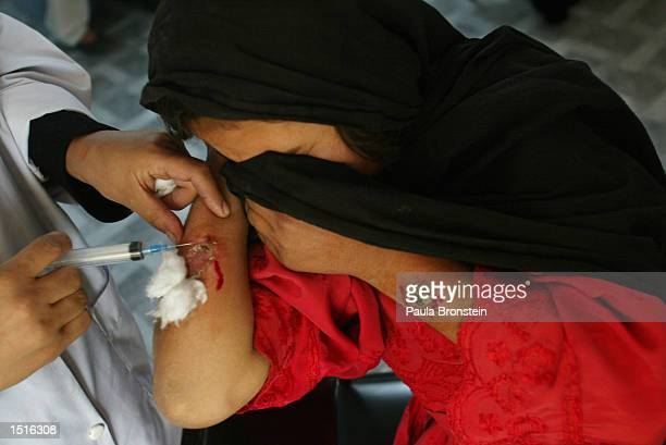 An Afghan girl gets treated for Leishmaniasis with an injection of Pentostam at the Health Net Clinic October 23, 2002 in Kabul, Afghanistan....
