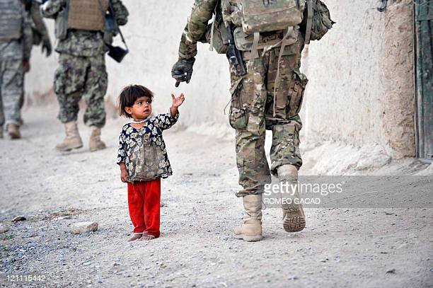 An Afghan girl greets a joint patrol of US troops from the Charlie Company 287 Infantry 3rd Brigade Combat Team and Afghan National Army soldiers at...