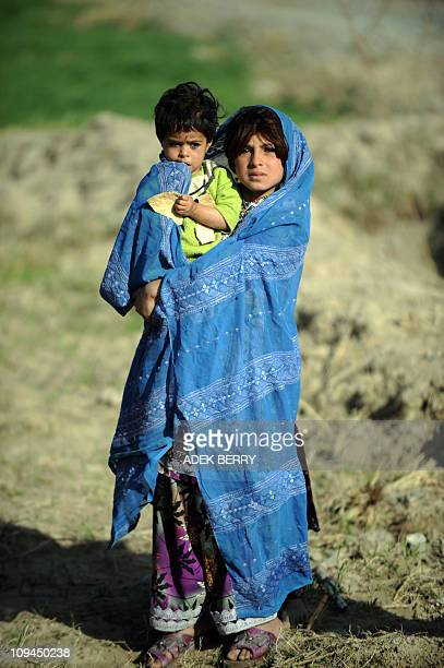 An Afghan girl holds a child as they watch US Marines of the 2nd Batallion 1st Marines Regiment during a patrol in Garmser Helmand Province...
