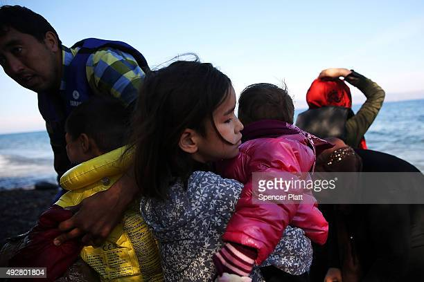 An Afghan girl holds a sibling on the beach moments after arriving by raft from Turkey on October 15 2015 in Sikaminias Greece Dozens of rafts and...