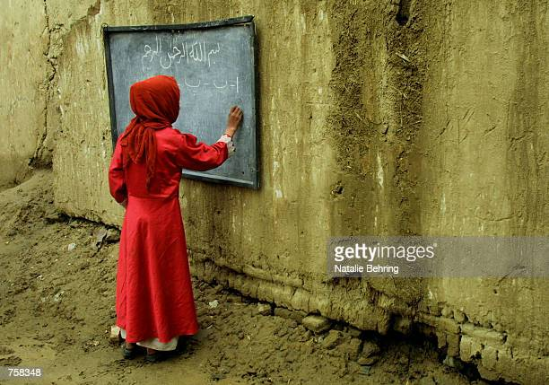 An Afghan girl learns the letters of the Dari alphabet on a blackboard in an outdoor classroom during a lesson on the first day of the official...