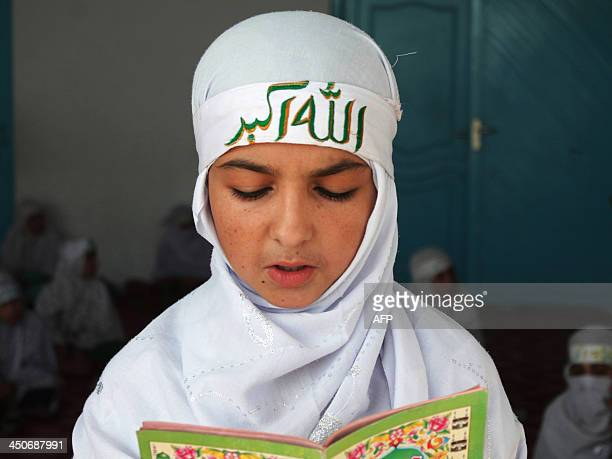 An Afghan girl learns to read the koran at a religious school in Kandahar on November 19 2013 The religious school called a Maktab offers free...
