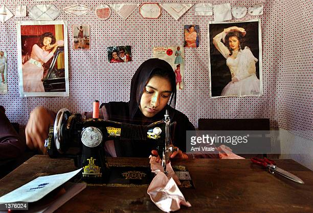 An Afghan girl learns to sew through a UN Habitat program September 10 2002 in Kabul Afghanistan Old magazines of Western and Indian models decorate...