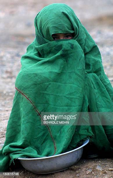 An Afghan girl line up for food distrebuted by UNICEF at Maslakh refugee camp 10 kms west of Herat in western Afghanistan 01 December 2001 Thousands...