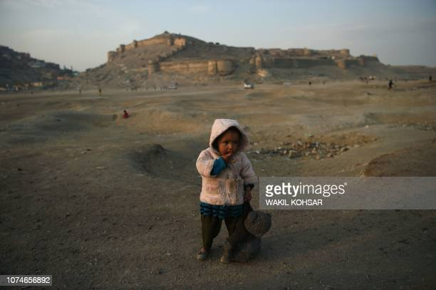 An Afghan girl looks on as she holds a soft toy bear at Shuhada Lake in Kabul on December 23 2018