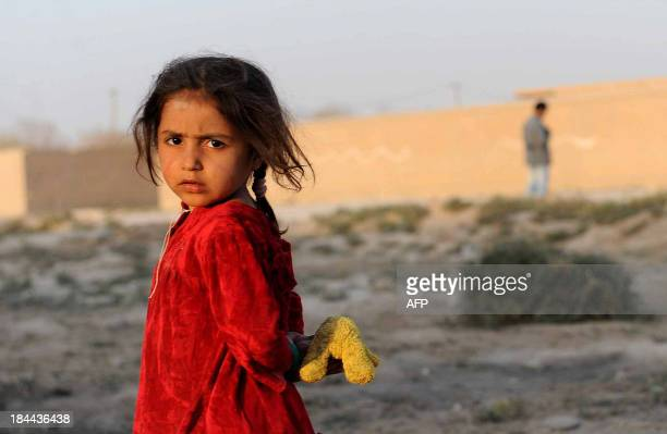 An Afghan girl looks on as she holds her doll on the outskirts of MazariSharif on October 13 2013 Some nine million Afghans or 36 percent of the...