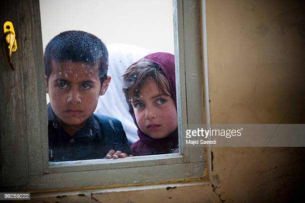An Afghan girl looks through a window of a class in a schoolhouse on May 13 2010 in Kabul Afghanistan Nine years after the collapse of Taliban...