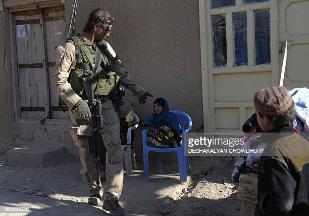 An Afghan girl looks up at a Dutch soldier of Charlie Air assault company as he gives her an orange during a patrol in a market place of Mirwais on...