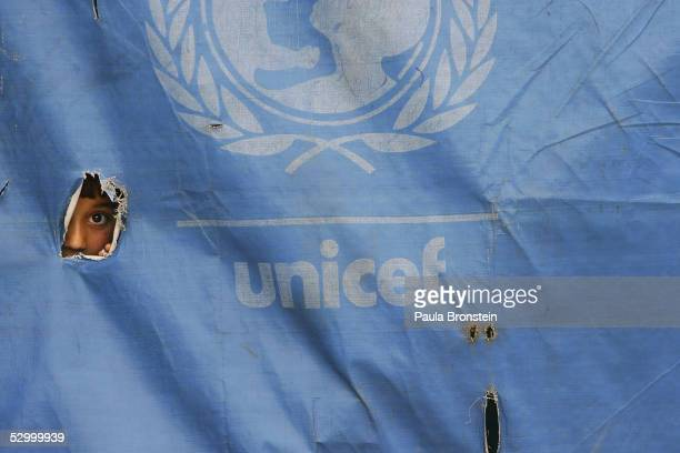An Afghan girl peeks out from a UNICEF school tent during class on May 30 2005 at a school in Faisabad in the Badakhshan district northeast of...