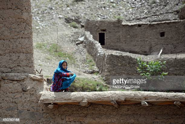 An Afghan girl sits on the roof of her house as she watches the flood in the Guzirga iNur district of Baghlan province on June 8 2014 Rescuers...