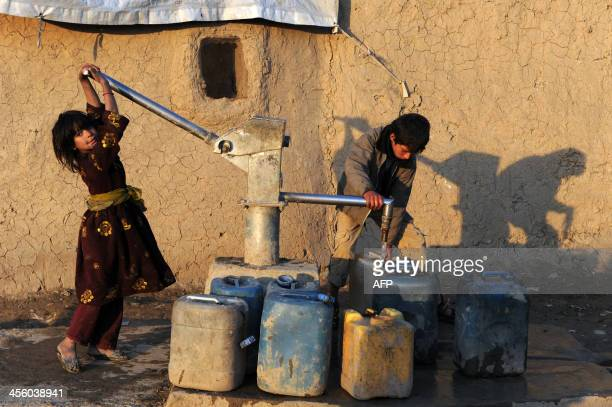 An Afghan girl smiles as she pumps water at a refugee camp located in Kabul on December 13 2013 Thousands of displaced people live in camps in and...