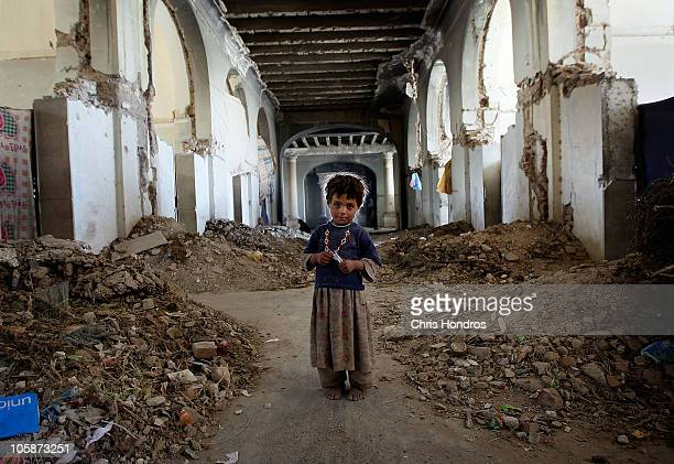 An Afghan girl stands in the ruins Darul Aman Palace October 21 2010 on the outskirts of Kabul Afghanistan A group of Afghan Kuchi tribal nomads...