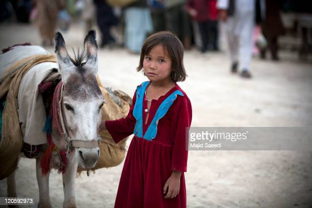 An Afghan girl stands near a donkey during the holy month of Ramadan on August 7 2011 in Kabul Afghanistan The Islamic holy month of Ramadan is...