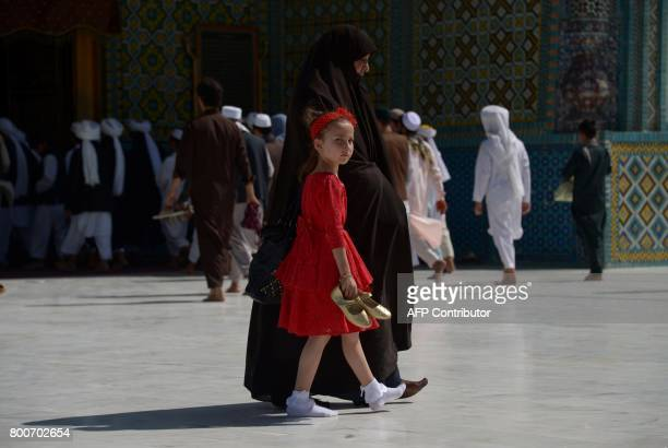 An Afghan girl walks with her mother through the courtyard of Hazrat Ali shrine or Blue Mosque during Eid alFitr prayers in MazariSharif on June 25...