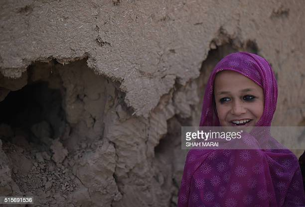 An Afghan girl watches Afghan National Army soldiers in DandeGhori district in Baghlan province on March 15 following weeks of heavy battles to...