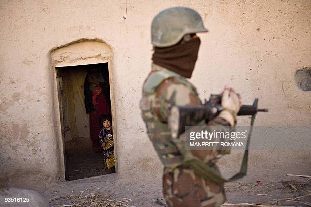 An Afghan girl watches from her house as Afghan National Army soldier stands guard during a search operation with US Marines of 2nd Battalion 2...