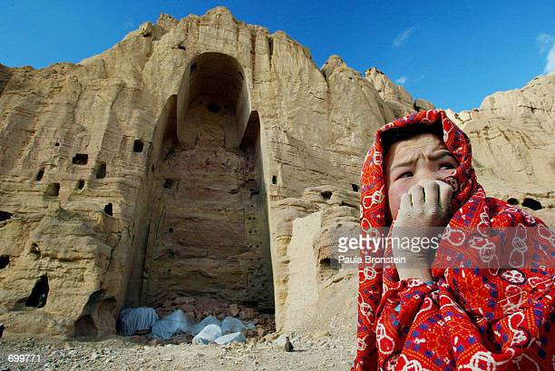 An Afghan girl who lives in nearby caves sits in front of the destroyed Buddha statue February 19 2002 in Bamiyan Afghanistan The ancient Buddhist...