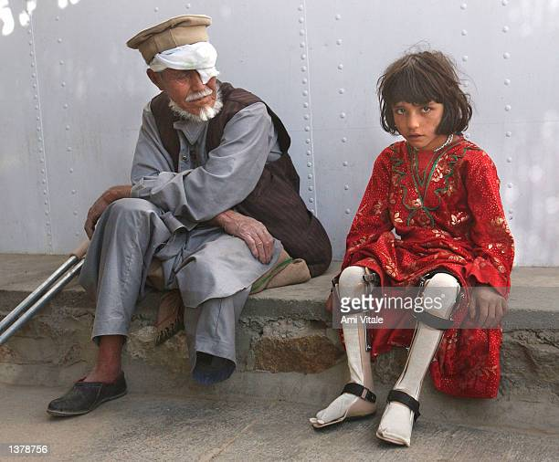An Afghan girl with polio and a man who lost his leg sit at an ICRC hospital September 11 2002 in Kabul Afghanistan Many Afghans are still living...