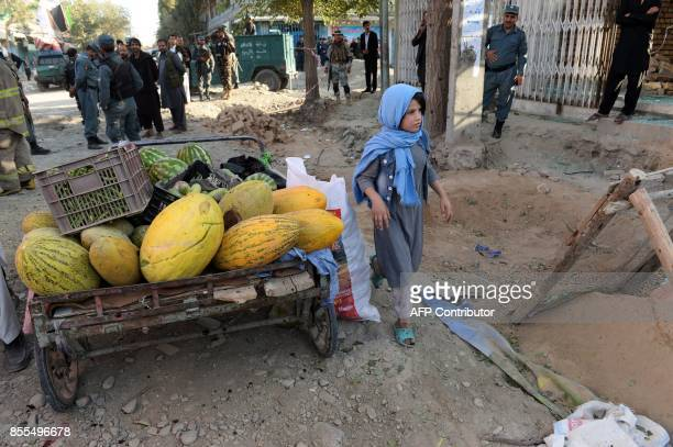 An Afghan girls walks past policemen standing guard at the site of a suicide bomb attack near a Shiite mosque in Kabul on September 29 2017 Up to six...