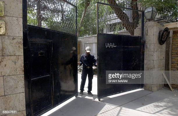 An Afghan guard opens the gate of the Italian Embassy prior to the departure of freed Italian hostage Clementina Cantoni departs for the...