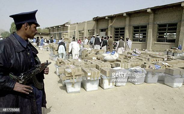 An Afghan guard stands alert beside ballot boxes filled with ballot papers from the country's presidential elections in the southern Afghan city of...