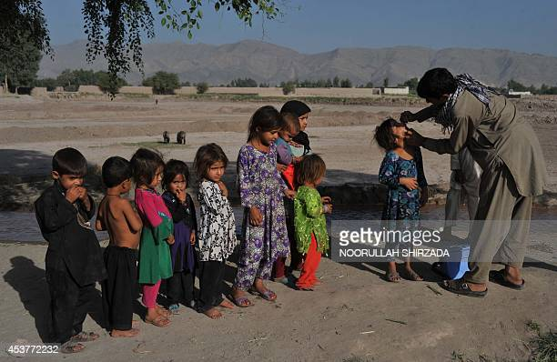 An Afghan health worker administers a polio vaccination to a child during a vaccination campaign on the outskirts of Jalalabad in Nangarhar province...