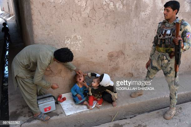 TOPSHOT An Afghan health worker administers polio drops to a child during a polio vaccination campaign in the Surkh Rod district of Nangarhar...