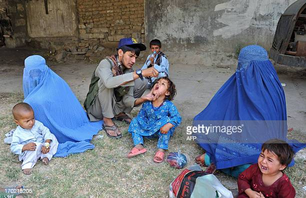 An Afghan health worker administers polio vaccination drops to a child during a vaccination campaign in Jalalabad capital of Nangarhar province on...